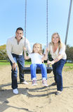Girl sitting on a swing, father on mother pushing Stock Photo