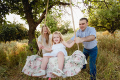 Girl sitting on a swing, father on mother pushing on nature,happy family, parents, smile, joy Stock Photos