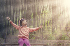 Girl sitting on a swing in the forest Royalty Free Stock Photo