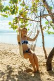 Girl sitting in swing hammock by the sea stock photography
