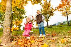 Girl sitting on swings and blond boy standing near Royalty Free Stock Image