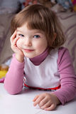 Girl sitting at the table Royalty Free Stock Photography