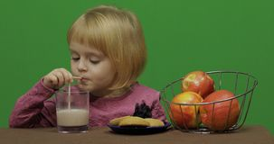 Girl sitting at the table with apples, cookies and drinks cacao. Chroma Key stock photography