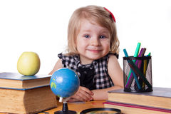 Girl sitting at table with books and globe Royalty Free Stock Photography