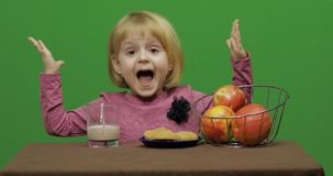 Girl sitting at the table with cacao, apples and cookies. Chroma Key royalty free stock photography