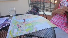 Girl sitting at a table with a city map stock footage