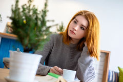 Girl sitting at a table with a cup of coffee Stock Photography