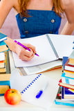 Girl sitting at table and doing homework. Closeup Royalty Free Stock Photography