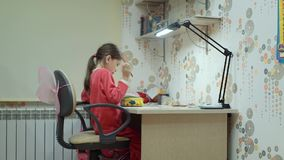 Girl sitting at a table draws on paper stock video footage