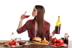 A girl sitting at a table with food, drinking red wine from a glass and holding a bottle of red wine. stock photography
