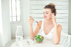 Portrait of a young smiling woman eating a fresh salad in white room. Stock Photography