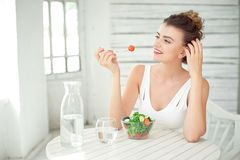 Portrait of a young smiling woman eating a fresh salad in white room. Stock Photos