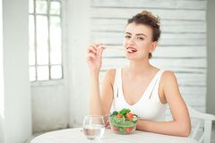 Portrait of a young smiling woman eating a fresh salad in white room. Royalty Free Stock Images