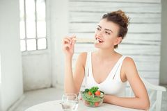 Portrait of a young healthy woman eating a crispbread in white room. Royalty Free Stock Photos