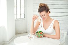 Portrait of a young smiling woman eating a fresh salad in white room. Royalty Free Stock Photography