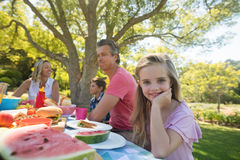 Girl sitting at the table with having meal whith her family in park Stock Photos
