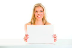 Girl sitting at table and holding blank paper Stock Photo