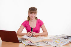 Girl sitting at table with laptop and newspaper Stock Photography