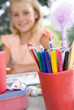 Girl (6-8) sitting at table with paints, smiling, portrait (focus on coloured markers in foreground) Stock Photography