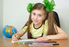 Girl sitting at a table with pencils Stock Image
