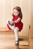 Girl sitting on table and put on one's shoes Royalty Free Stock Image