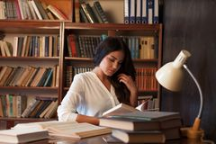 Girl sitting at the table reading a book is preparing for the exam stock image