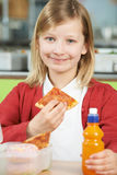 Girl Sitting At Table In School Cafeteria Eating Unhealthy Packe Royalty Free Stock Photography