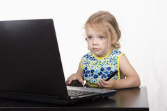 The girl sitting at the table, working at a laptop, and holding a pen Royalty Free Stock Photos