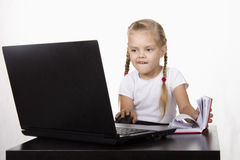 The girl sitting at the table, working at a laptop, and records in a notebook Stock Photography