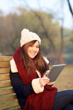 Girl sitting with tablet on bench in park Stock Photography