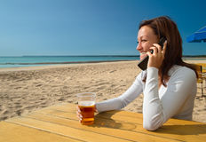 Girl sitting&talking by phone on a beach. Beach cafe scenics Stock Photos
