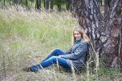 Girl sitting in tall grass near a pine tree. Stock Photography
