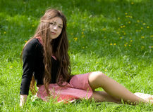 Girl sitting in th park. Attractive girl with long brown hair is sitting on the grass in the park Royalty Free Stock Photography