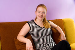 Girl sitting on ther sofa Stock Photography