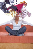 Girl sitting and throwing clothes in the air Royalty Free Stock Images
