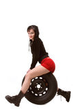 Girl sitting on tire. Smiling brunette girl in red shorts and leather boots sitting on car tire Stock Photo