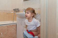 Girl sitting on   toilet Stock Photo