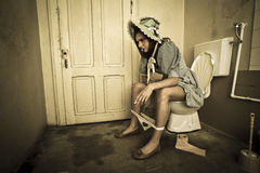 Girl sitting on the toilet Royalty Free Stock Photo
