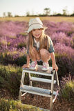 Girl sitting on top stepladder outdoors Stock Image