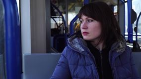 Girl sitting in a tram to Amsterdam and looks out the window. Girl rides a tram to Amsterdam and looks out the window stock footage