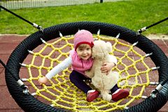 Girl sitting at trampoline with toy dog Stock Photo