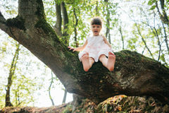 Girl sitting on a tree. foot. Played with their feet.  Stock Photos