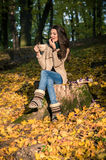 Girl sitting on tree stump Stock Photos
