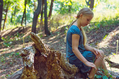 Girl sitting on a tree stump Stock Photo