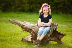Girl sitting on a tree trunk Stock Image