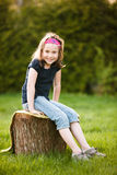 Girl sitting on a tree trunk Stock Images