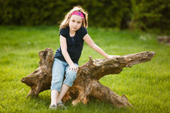 Girl sitting on a tree trunk Royalty Free Stock Image