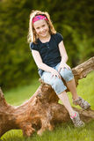 Girl sitting on a tree trunk Royalty Free Stock Photography