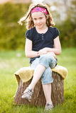 Girl sitting on a tree trunk Royalty Free Stock Photos