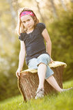 Girl sitting on a tree trunk stock photo